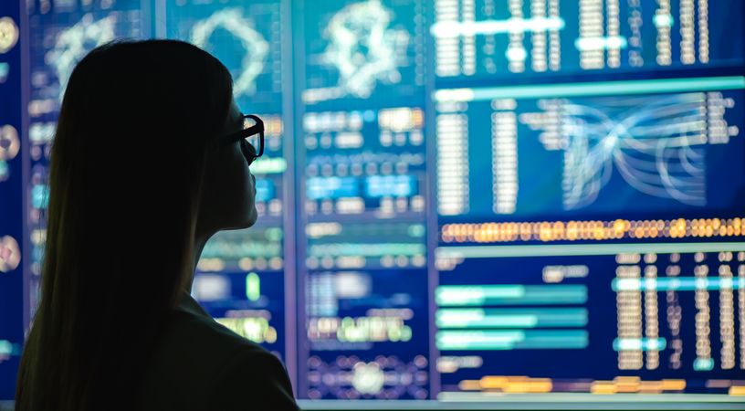 Woman in silhouette looking at large screens