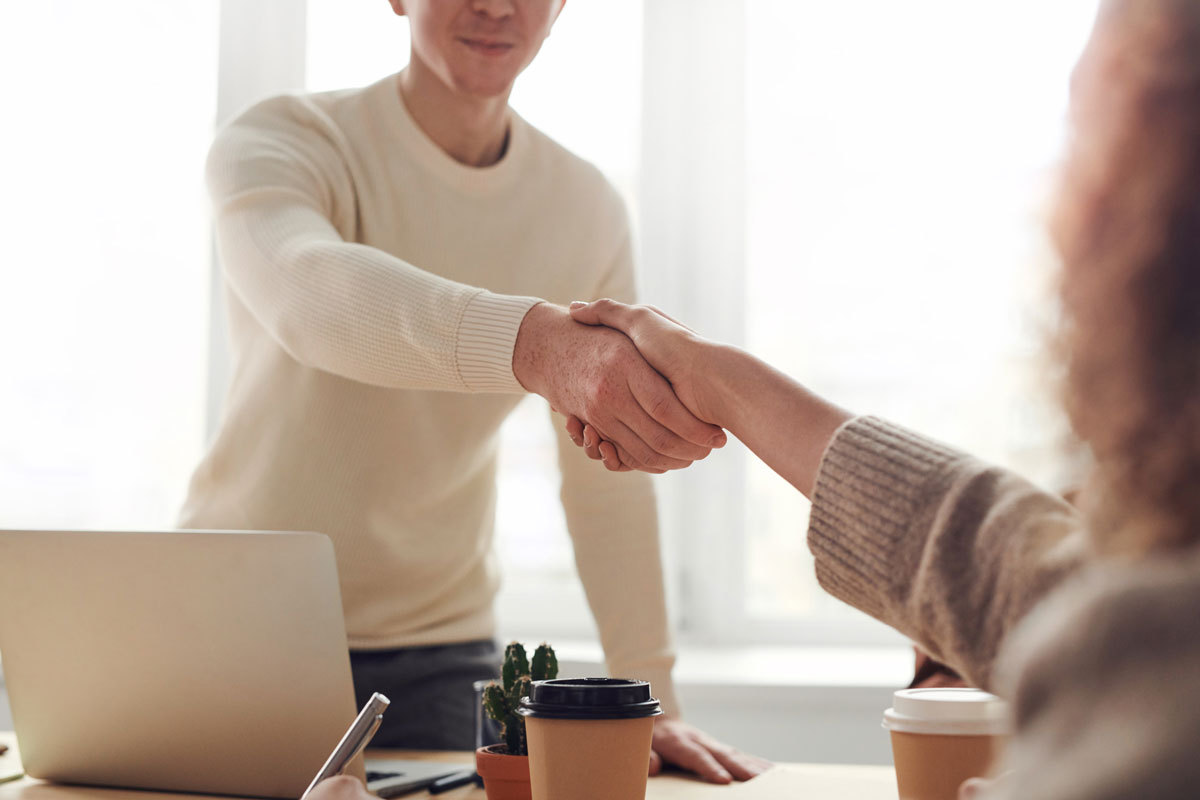 candidate shaking interviewers hand in competency based interview