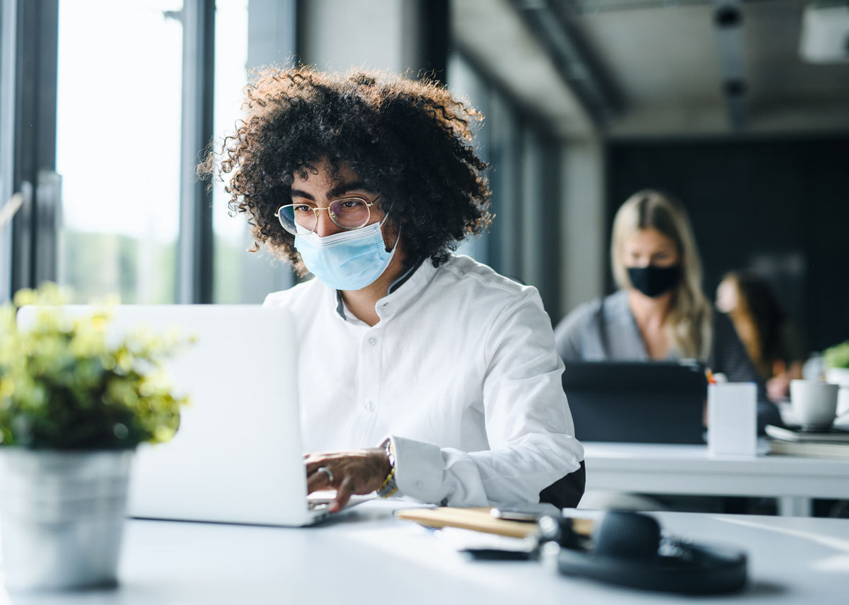 man sat at a laptop wearing a mask to protect against the coronavirus